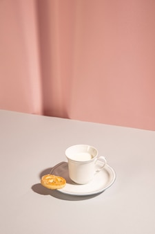 Leche fresca con galleta dulce en la mesa contra el fondo rosa
