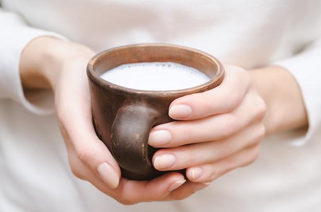 Leche fresca en una taza de arcilla en manos femeninas