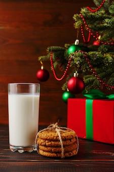 Leche, galletas y regalos bajo el árbol de navidad. el de la llegada de santa claus.