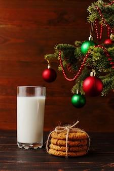 Leche y galletas para santa claus bajo el árbol de navidad. copyspace