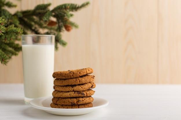Leche y galletas para santa claus bajo el árbol de navidad