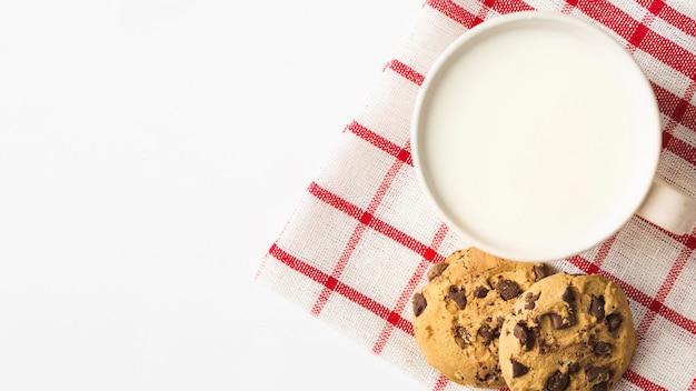 Leche con galletas en la servilleta sobre el fondo blanco