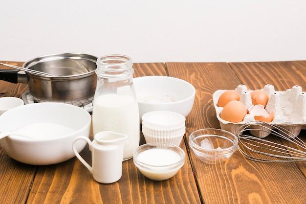 Leche; huevo; y utensilios de cocina en el mostrador de la cocina.