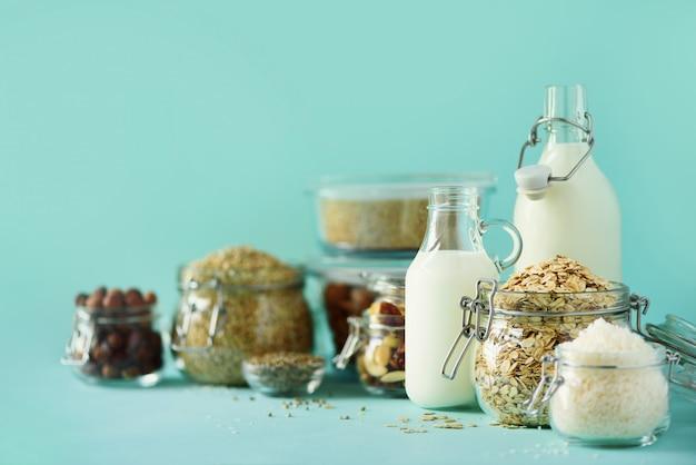 Leche láctea sustituto vegano. botellas de vidrio con leche e ingredientes no lácteos sobre fondo azul con espacio de copia.