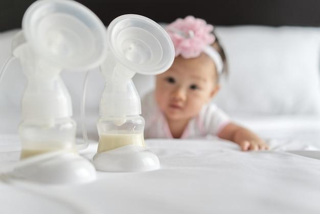 Leche materna en las botellas de la bomba de leche en la cama con el pequeño bebé lindo que se arrastra en el fondo.