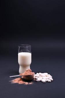 Leche y nutrición deportiva sobre un fondo negro. proteínas y complementos alimenticios. espacio libre para texto. copia espacio
