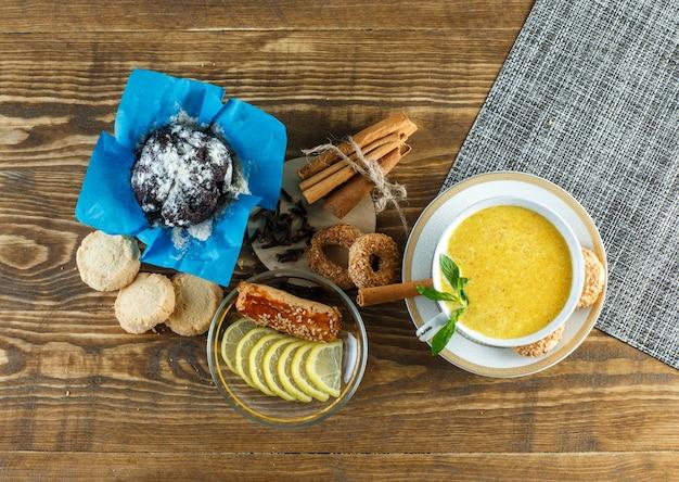 Leche picante en una taza con menta, galletas, clavo, rodajas de limón, canela, vista superior en mesa de madera