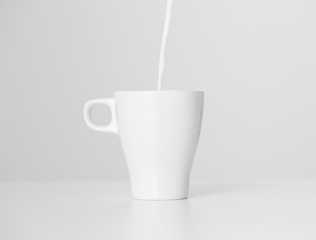 Leche de primer plano vertiendo en una taza de cerámica