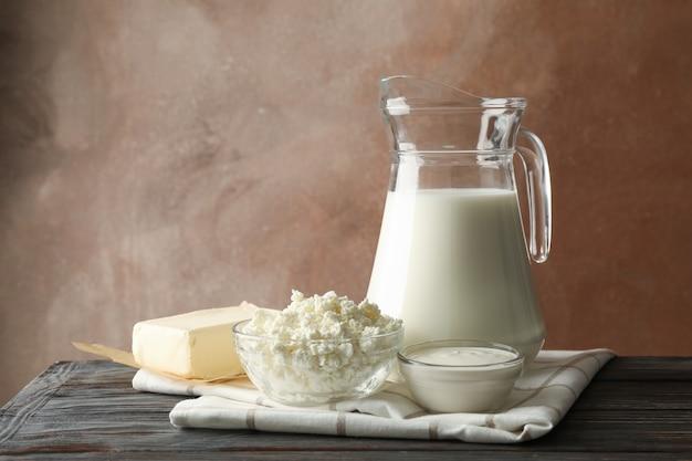 Leche, requesón y mantequilla en la mesa de madera sobre fondo marrón