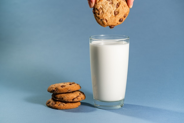 Leche con splash y cookies de sabor chocolate sobre fondo azul.