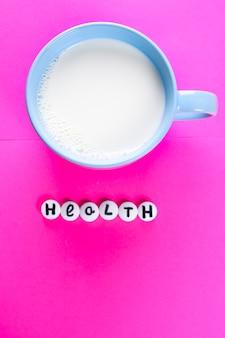 Leche en taza azul e inscripción salud de píldoras médicas blancas