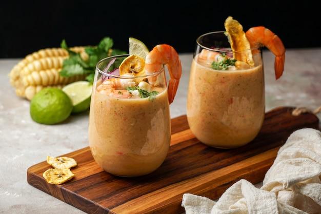 Leche de tigre, comida peruana, ecuatoriana, latinoamericana, ceviche de cóctel de pescado crudo con lima, aji limón y cilantro. comida tradicional peruana con srimps y chips de plátano