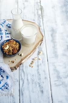 Leche en un vaso y en una botella, muesli en una taza azul y piña y mantel con flores azules