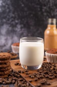 Leche en un vaso, completa con granos de café, pastelitos, plátanos y galletas en un plato de madera.