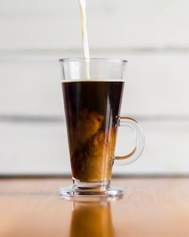 Leche vertiendo en café caliente