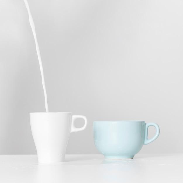 Leche vertiendo en una taza de cerámica sobre una mesa