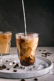Leche vertiendo en vaso de café