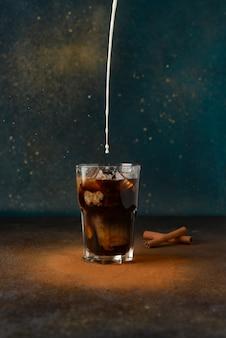 La leche se vierte en una taza de vidrio con café frío.