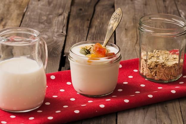 Leche, yogur y avena seca en el frasco de vidrio en la servilleta roja sobre la mesa de madera