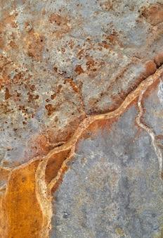 Lecho de río oxidado seco sobre relaves de mina gris, textura vertical de drenaje de mina ácida