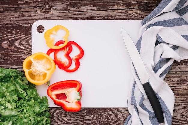 Lechuga y pimientos en una tabla de cortar blanca con cuchillo y servilleta sobre el escritorio de madera