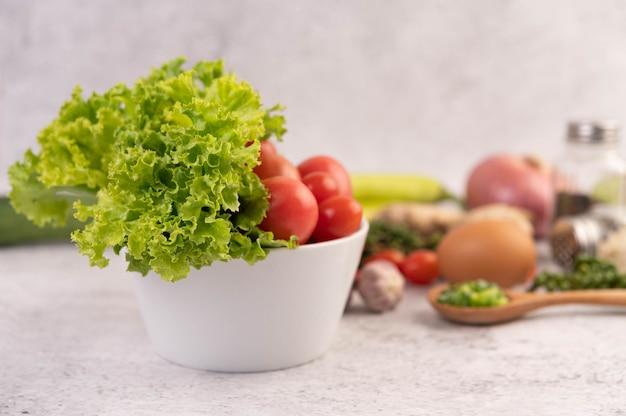 Lechuga y tomates en una taza blanca con rodajas de cebolla y pimientos frescos en el piso de cemento.