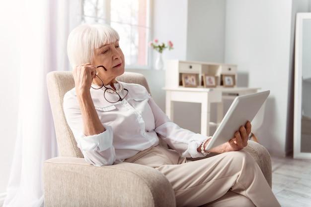 Lector atento. agradable dama senior leyendo pensativamente desde una tableta, habiéndose quitado las gafas, mientras está sentada en el sillón