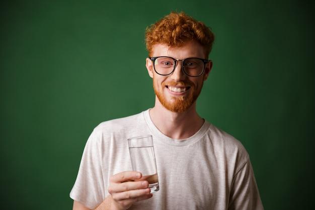 Lectura alegre hombre barbudo con gafas, sosteniendo un vaso de agua,