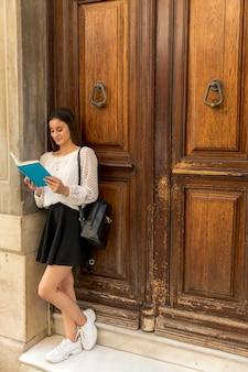 Lectura sonriente joven de la señora cerca de puertas de madera