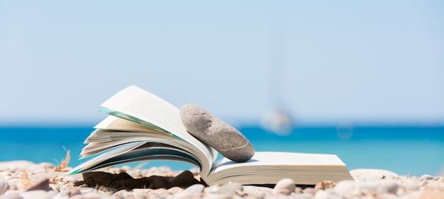 Lectura en vacaciones de verano, concepto. libro en la playa de guijarros.
