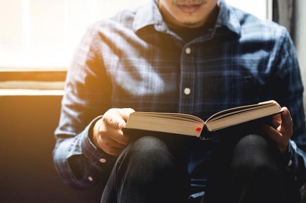 Lecturas dominicales, biblia. joven sentado leyendo la biblia en la sala. espacio de copia