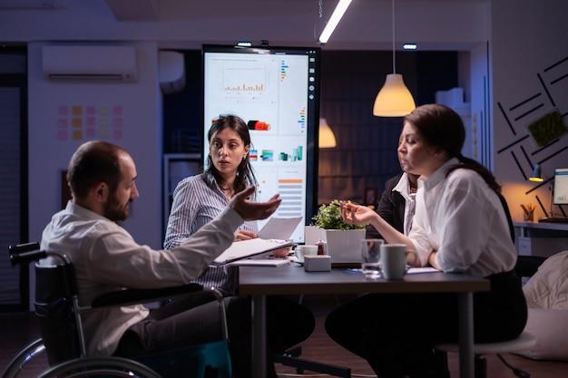Leder discapacitado paralizado en silla de ruedas explicando las estadísticas de la empresa sobre el trabajo en la oficina ...