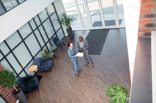 Leer el acuerdo. vista superior de empresarios leyendo el acuerdo después de la reunión en el espacioso centro de oficinas