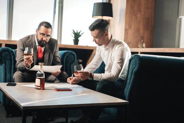 Leer documentos. los empresarios sentados en cómodos sillones bebiendo una botella de coñac mientras leen documentos