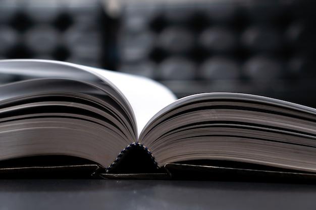 Leer libros de texto antiguos en la biblioteca de la universidad, leer libros o relajarse en negro vintage