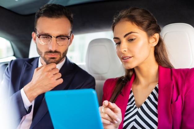 Leer noticias financieras. pareja de jóvenes empresarios prósperos leyendo noticias financieras en el camino al trabajo
