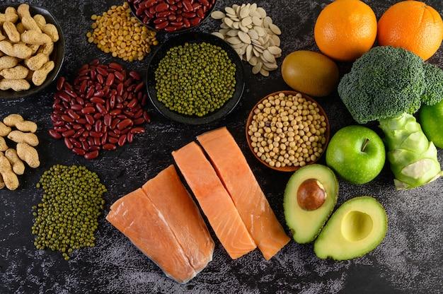Legumbres, brócoli, fruta y salmón colocados en un piso de cemento negro.