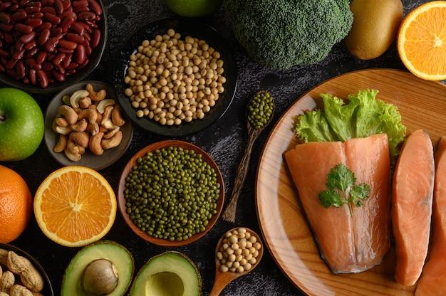 Legumbres, trozos de fruta y salmón en un plato de madera.