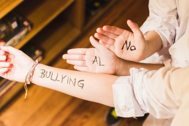 Lema contra la intimidación escrito en las manos de los niños
