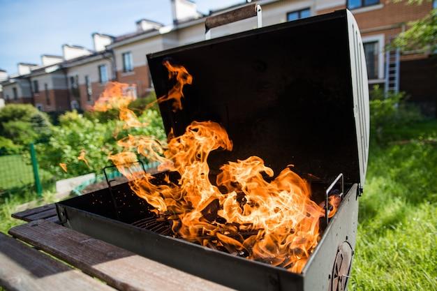 La leña arde fuertemente en la calle en verano. preparándose para una barbacoa.