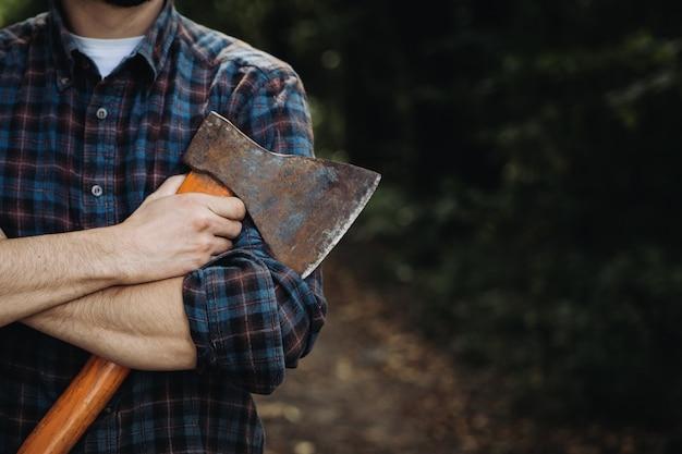 Leñador barbudo fuerte sosteniendo un hacha en el bosque