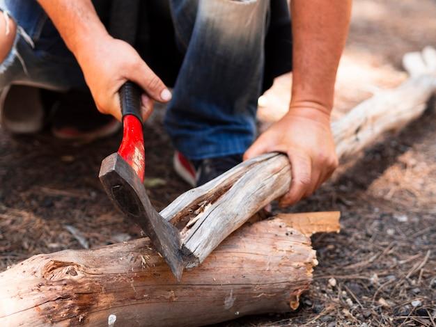 Leñador sin rostro cortando troncos en el bosque