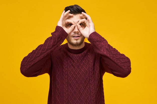 Lenguaje corporal y expresiones faciales humanas. varón joven juguetón alegre en suéter que conecta los pulgares y los dedos índice, haciendo círculos alrededor de los ojos, mirando a través de agujeros como usando binoculares, espiando