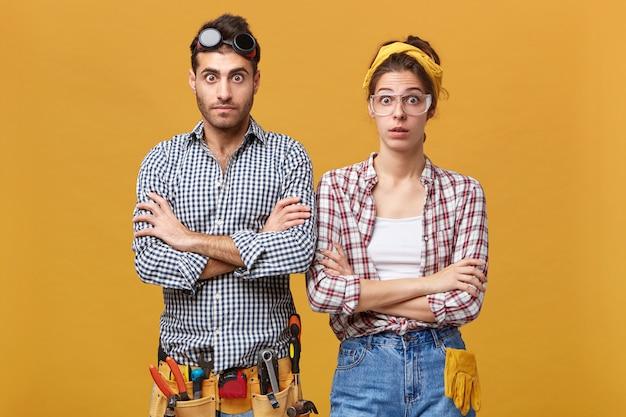 Lenguaje corporal. retrato de artesanos o electricistas que han sorprendido miradas de asombro, manteniendo los brazos cruzados y levantando las cejas, sorprendidos con algo. concepto de trabajo, ocupación y profesión.
