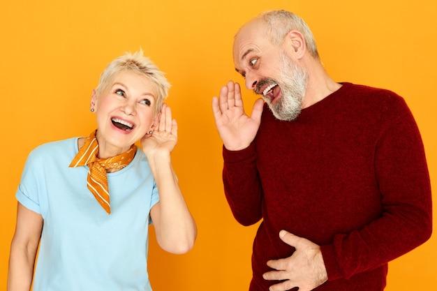 Lenguaje corporal. retrato de dos jubilados caucásicos ancianos divertidos con problemas de audición conversando, manteniendo las manos en la oreja y gritando, pero no pueden distinguir ninguna palabra. concepto de sordera