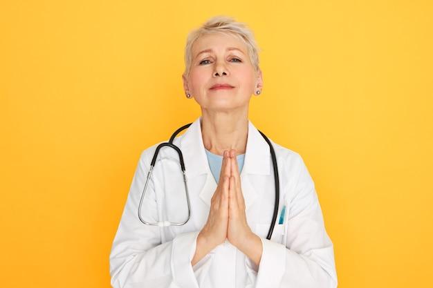 Lenguaje corporal. retrato de triste infeliz cirujana de mediana edad en uniforme médico con mirada triste, presionando las manos juntas, rezando, esperando que el paciente terminal se recupere