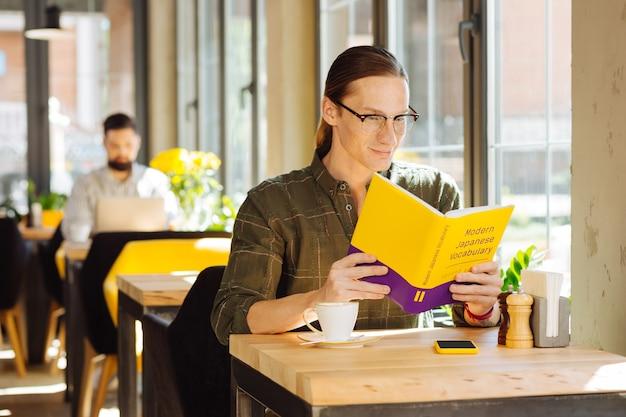 Lenguaje difícil. hombre positivo guapo leyendo un libro mientras estudia vocabulario japonés