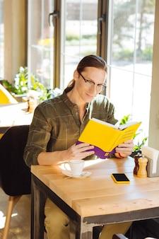 Lenguaje interesante. hombre inteligente alegre leyendo un libro mientras quiere aprender japonés