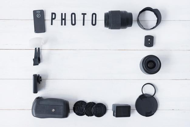 Lente de la cámara con accesorios de fotografía y texto de fotos dispuestas en una mesa de madera blanca