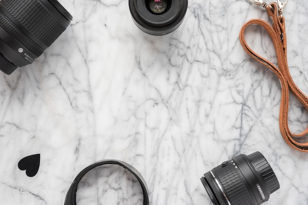 Lente de cámara profesional; anillos de extensión con forma de corazón y cinturón sobre suelo de mármol.